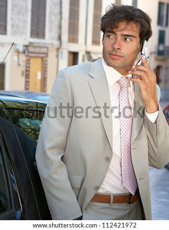 Businessman using a cell phone to make a phone call while standing by a car in the city. - stock photo