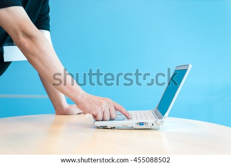 Businessman using a desktop compute in front of blue background