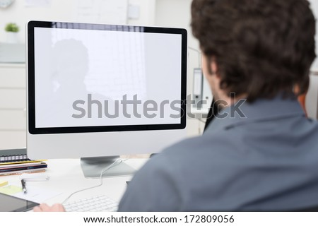 Businessman using a desktop computer with a view over his shoulder from behind of the blank screen of the monitor - stock photo