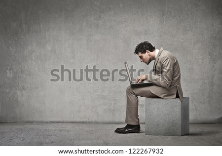 Businessman using a laptop computer sitting on a concrete block - stock photo