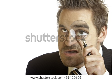 Businessman using a magnifying lense to analyze the problem - stock photo