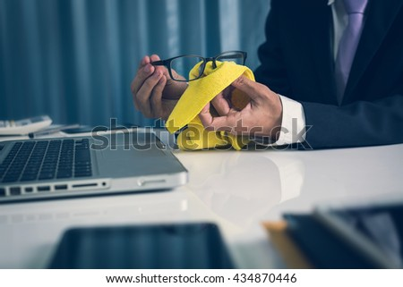 Businessman using a microfiber yellow cloth to clean the glasses in the office during working job at his desk hipster picture view vintage style. - stock photo