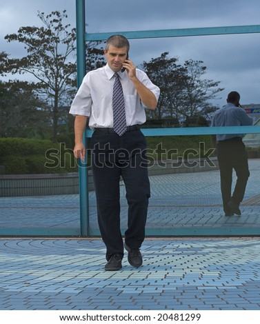 Businessman using a mobile phone in front of a corporate building.