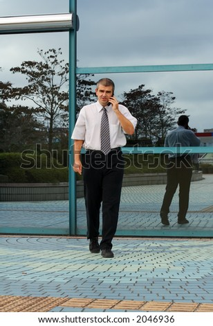 Businessman using a mobile phone while is walking in front of some blue corporate building windows.