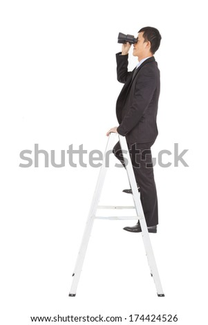 businessman using a pair of binoculars standing  on stair