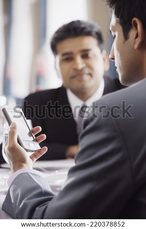 Businessman using a PDA in restaurant