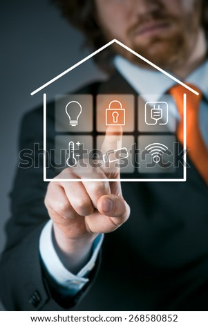 Businessman using a smart house control panel activating the security setting on a transparent virtual interface - stock photo