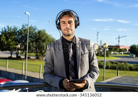 Businessman using a tablet and headphones while smiling - stock photo