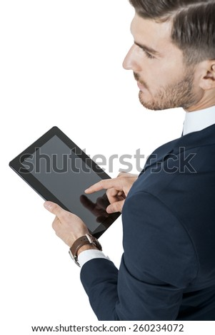 Businessman using a tablet computer navigating the touchscreen with his finger as he surfs the internet, close up view of his hands and the tablet, on white