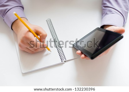 Businessman using a tablet pc and write something