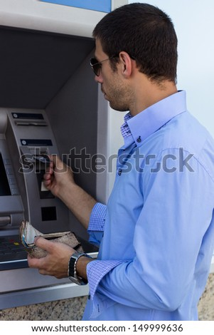 Businessman using ATM. Man put credit card into ATM - stock photo