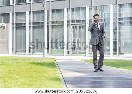Businessman using cell phone while walking on path outside office - stock photo