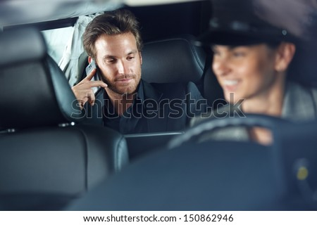 Businessman using cellphone in limousine, female chauffeur driving. - stock photo