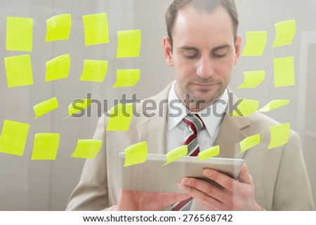 Businessman Using Digital Tablet In Front Of Adhesive Notes On Glass Wall