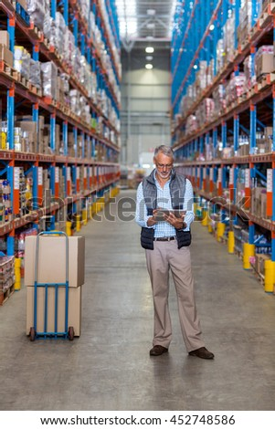 Businessman using digital tablet in warehouse