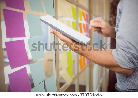 Businessman using digital tablet over white background against colorful adhesive notes - stock photo