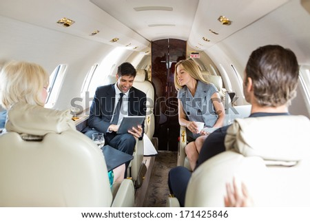 Businessman using digital tablet with colleagues in private jet - stock photo