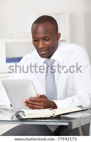 Businessman using electronic tablet in office - stock photo