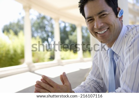 Businessman using hands-free device outdoors - stock photo