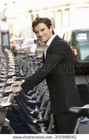 Businessman using hire bike - stock photo