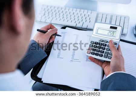 Businessman using his calculator in his office - stock photo