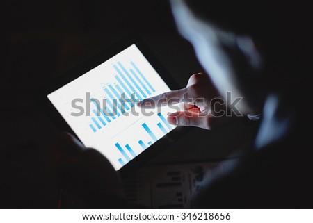 Businessman using his computer and looking at graphs