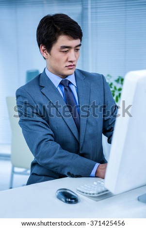 Businessman using his computer in his office - stock photo