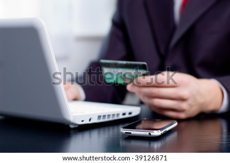 Businessman using his credit card for an online transaction