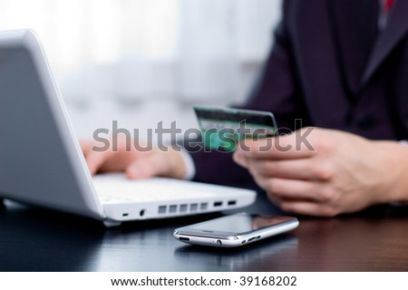 Businessman using his credit card for an online transaction - stock photo