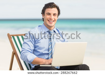 Businessman using his laptop at the beach - stock photo