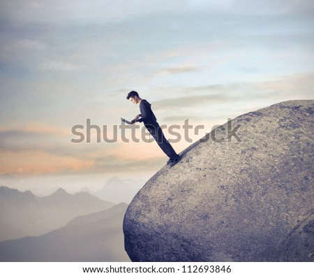 Businessman using his laptop computer on a raked rock - stock photo