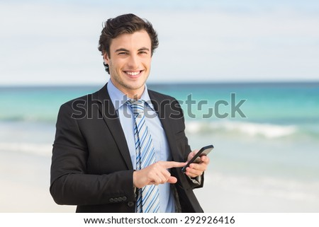 Businessman using his smartphone at the beach - stock photo