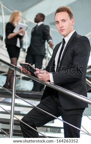 Businessman using his tablet in the office on the background of colleagues - stock photo