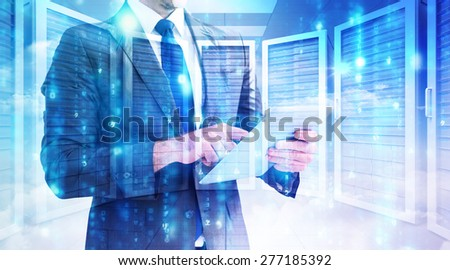 Businessman using his tablet pc against server room - stock photo