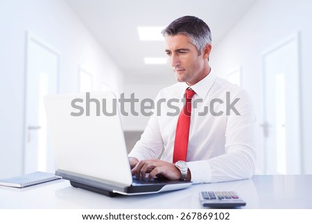 Businessman using laptop against bright hallway with several doors - stock photo
