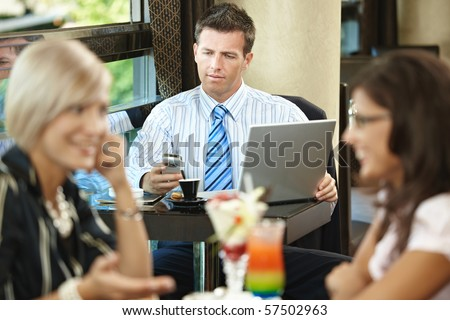 Businessman using laptop and mobile in cafe, young woman eating sweets and talking in the foreground. Selective focus on businessman. - stock photo