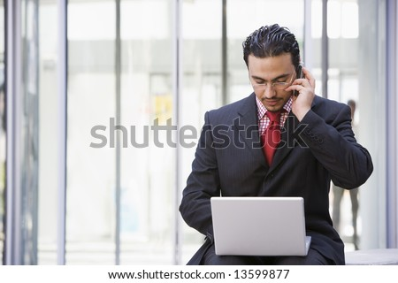 Businessman using laptop and mobile outside office - stock photo