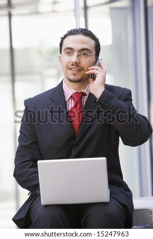 Businessman using laptop and mobile phone outside office - stock photo