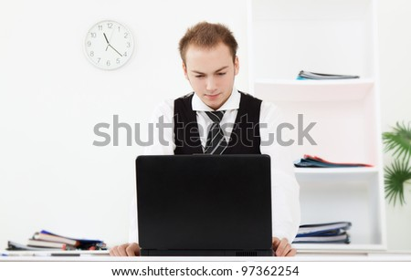 businessman using laptop at the desk in office, handsome young business man working on computer