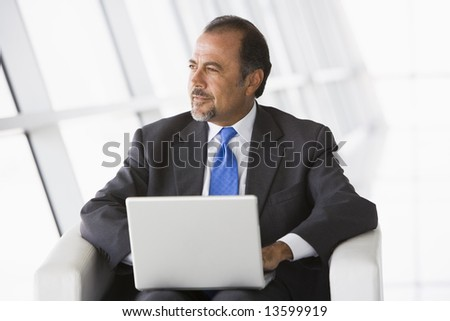 Businessman using laptop in office lobby - stock photo