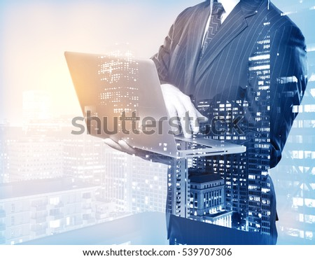 Businessman using laptop on city background. Double exposure. Communication concept
