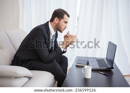 Businessman using laptop on his couch at home in the living room