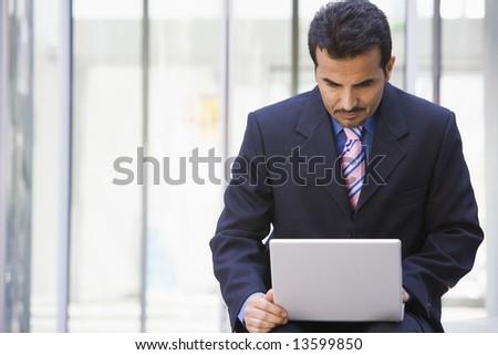 Businessman using laptop outside office - stock photo