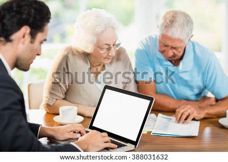Businessman using laptop while senior couple is reading documents at home