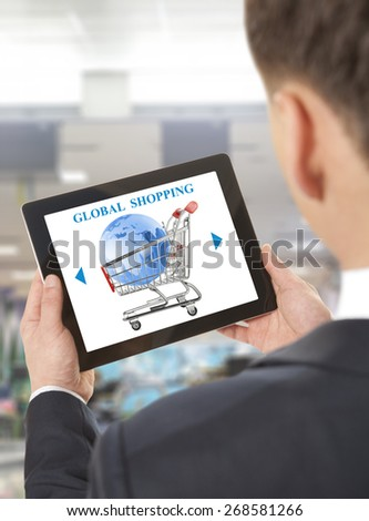 Businessman using laptop with online global shopping cart on screen
