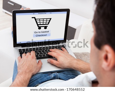Businessman Using Laptop With Online Shopping Application On A Screen - stock photo