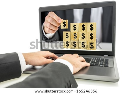 Businessman using laptop with structure on wooden cubes with dollar sign on monitor screen. Concept of online earnings. - stock photo