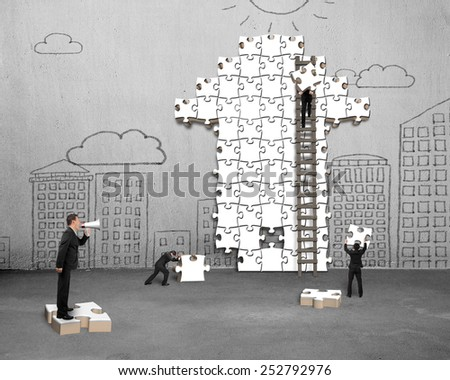 Businessman using megaphone commanding workers to build arrow jigsaw puzzle with doodles concrete wall background - stock photo