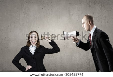 Businessman using megaphone to scream agressively at woman - stock photo