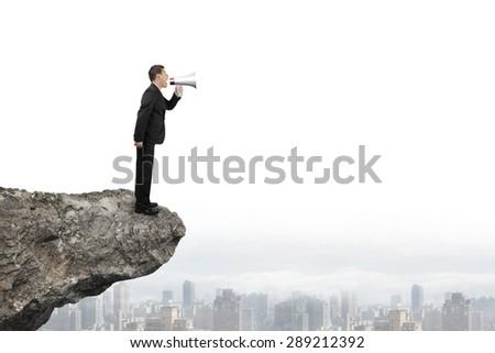Businessman using megaphone yelling on cliff with city skyline background - stock photo